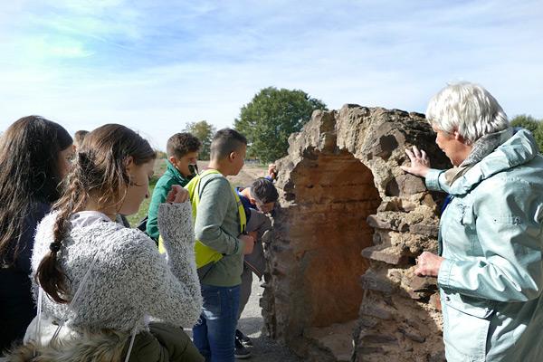 Die Museumsführerin erläutert Überreste der Wasserleitung.