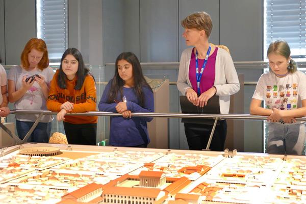 Eine Museumsführerin mit unseren Sechsern vor dem Stadtmodell.