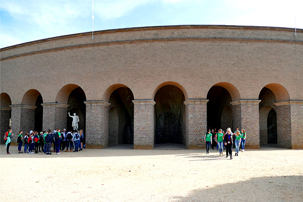 SchülerInnengruppen vor der wiederaufgebauten Arena mit der Statur des Kaisers Trajan.